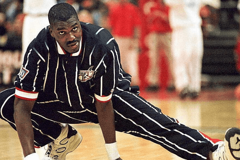 """LANDOVER, MD - DECEMBER 1: Houston Rockets center Hakeem Olajuwon stretches out before Houston's game against the Washington Bullets in Landover, Maryland 30 November. For the second time in two weeks, Olajuwon has been hospitalized with an irregular heartbeat. Olajuwon checked into a Houston hospital early 01 December where his condition was listed as """"very good."""""""