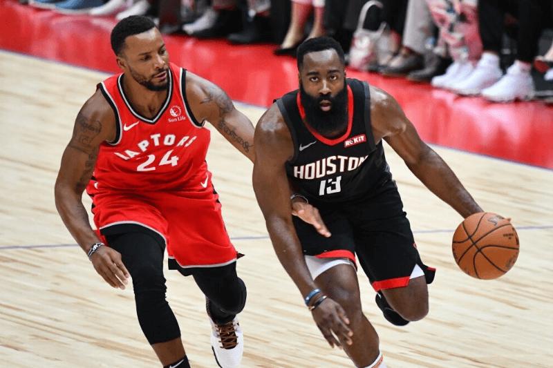 Houston Rockets James Harden (R) dribbles the ball next to Toronto Raptors Norman Powell (L) during their NBA preseason basketball game in Saitama on October 8, 2019.