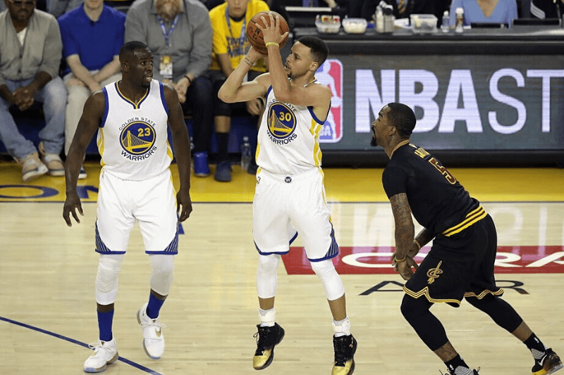 OAKLAND, CA - JUNE 19: Stephen Curry #30 of the Golden State Warriors shoots the ball as Draymond Green #23 and J.R. Smith #5 of the Cleveland Cavaliers look on during the first half in Game 7 of the 2016 NBA Finals at ORACLE Arena on June 19, 2016 in Oakland, California.