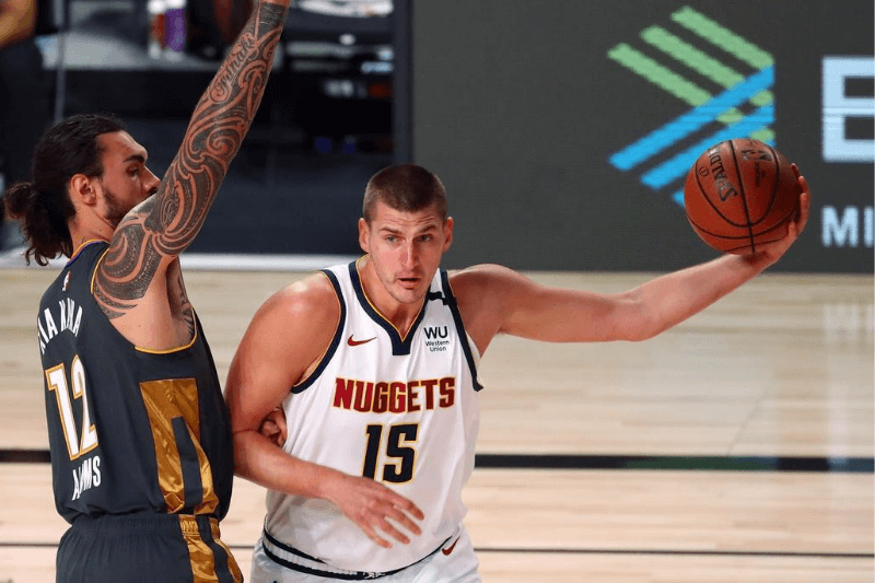 Aug 3, 2020; Lake Buena Vista, Florida, USA; Denver Nuggets center Nikola Jokic (15) drives to the basket against Oklahoma City Thunder center Steven Adams (12) during the first quarter in a NBA basketball game at The Arena.
