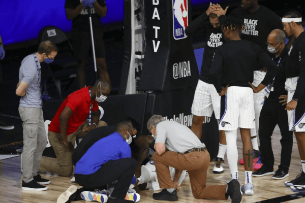Aug 2, 2020; Lake Buena Vista, Florida, USA; Orlando Magic forward Jonathan Isaac (1) is looked at by medical staff members after an injury against the Sacramento Kings in the second half of a NBA basketball game at HP Field House.