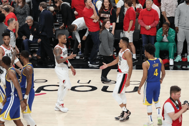 May 20, 2019; Portland, OR, USA; Portland Trail Blazers guard Damian Lillard (0) and Trail Blazers' guard CJ McCollum (3) approach each other after losing to the Golden State Warriors 119-117 in overtime in game four of the Western conference finals of the 2019 NBA Playoffs at Moda Center.