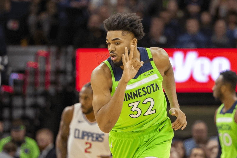 Feb 8, 2020; Minneapolis, Minnesota, USA; Minnesota Timberwolves center Karl-Anthony Towns (32) holds up three fingers after making a three point shot in the first half against the LA Clippers at Target Center