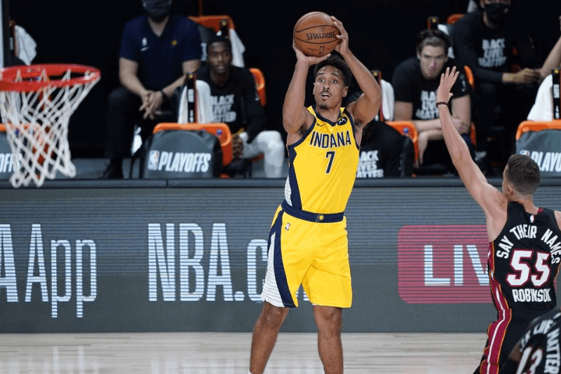 Aug 18, 2020; Lake Buena Vista, Florida, USA; Indiana Pacers guard Malcolm Brogdon (7) shoots past Miami Heat guard Duncan Robinson (55) during the first half of an NBA basketball first round playoff game, Tuesday, Aug. 18, 2020, in Lake Buena Vista, Fla