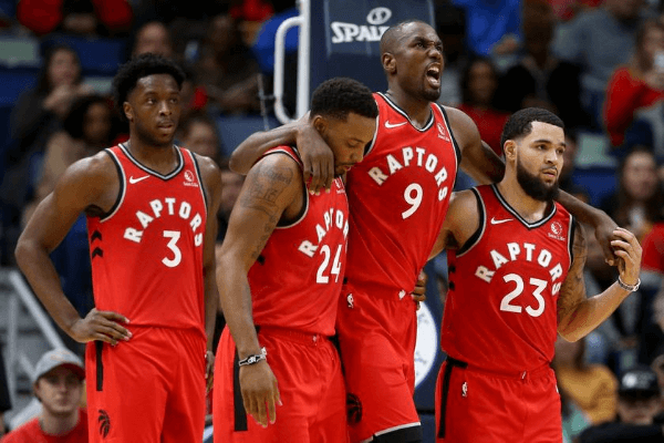 Nov 8, 2019; New Orleans, LA, USA; Toronto Raptors forward Serge Ibaka (9) is helped off the court by guards Norman Powell (24) and Fred VanVleet (23) in the second quarter against the New Orleans Pelicans at the Smoothie King Center