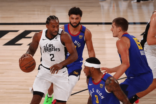 Aug 12, 2020; Lake Buena Vista, Florida, USA; LA Clippers forward Kawhi Leonard (2) is defended by Denver Nuggets center Nikola Jokic (15) in the first quarter of a NBA basketball game at AdventHealth Arena.