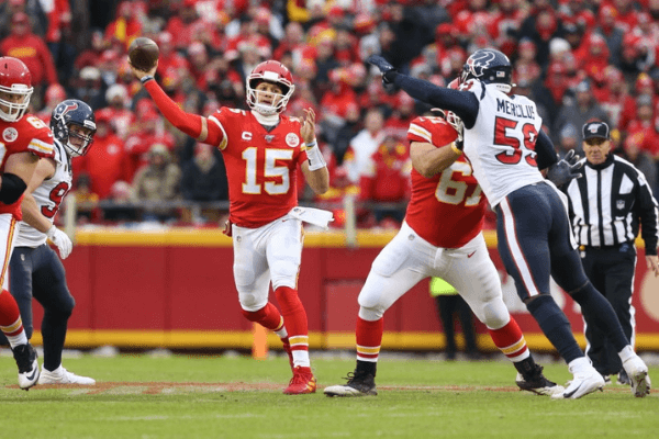 KANSAS CITY, MO - JANUARY 12: Kansas City Chiefs quarterback Patrick Mahomes (15) throws a 25-yard completion to tight end Travis Kelce (87) past the outstretched arms of Houston Texans outside linebacker Whitney Mercilus (59) in the second quarter of an NFL Divisional round playoff game between the Houston Texans and Kansas City Chiefs on January 12, 2020 at Arrowhead Stadium in Kansas City, MO.