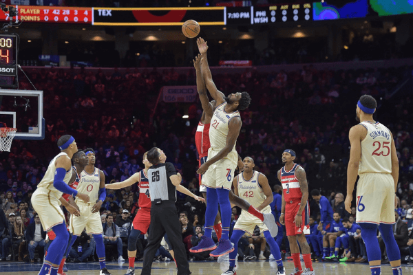 Dec 21, 2019; Philadelphia, Pennsylvania, USA; Philadelphia 76ers center Joel Embiid (21) and Washington Wizards center Ian Mahinmi (28) compete for the opening tap to start the first quarter of the game at the Wells Fargo Center. Mandatory Credit: John Geliebter-USA TODAY Sports