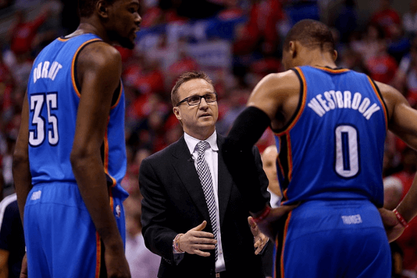Head coach Scott Brooks of the Oklahoma City Thunder talks with Russell Westbrook #0 and Kevin Durant #35 against the Los Angeles Clippers in Game Three of the Western Conference Semifinals during the 2014 NBA Playoffs at Staples Center on May 9, 2014 in Los Angeles, California. The Thunder won 118-112. NOTE TO USER: User expressly acknowledges and agrees that, by downloading and or using this photograph, User is consenting to the terms and conditions of the Getty Images License Agreement.
