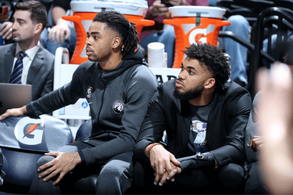 D'Angelo Russell #0 of the Minnesota Timberwolves and Karl-Anthony Towns #32 of the Minnesota Timberwolves look on during a game against the Charlotte Hornets on February 12, 2020 at Target Center in Minneapolis, Minnesota.