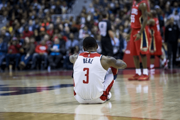 Washington Wizards' Bradley Beal (3) sits on the court after calling for an injury during the NBA match between Washington Wizards and New Orleans Pelicans at the Capital One Arena in Washington, United States on December 19, 2017.