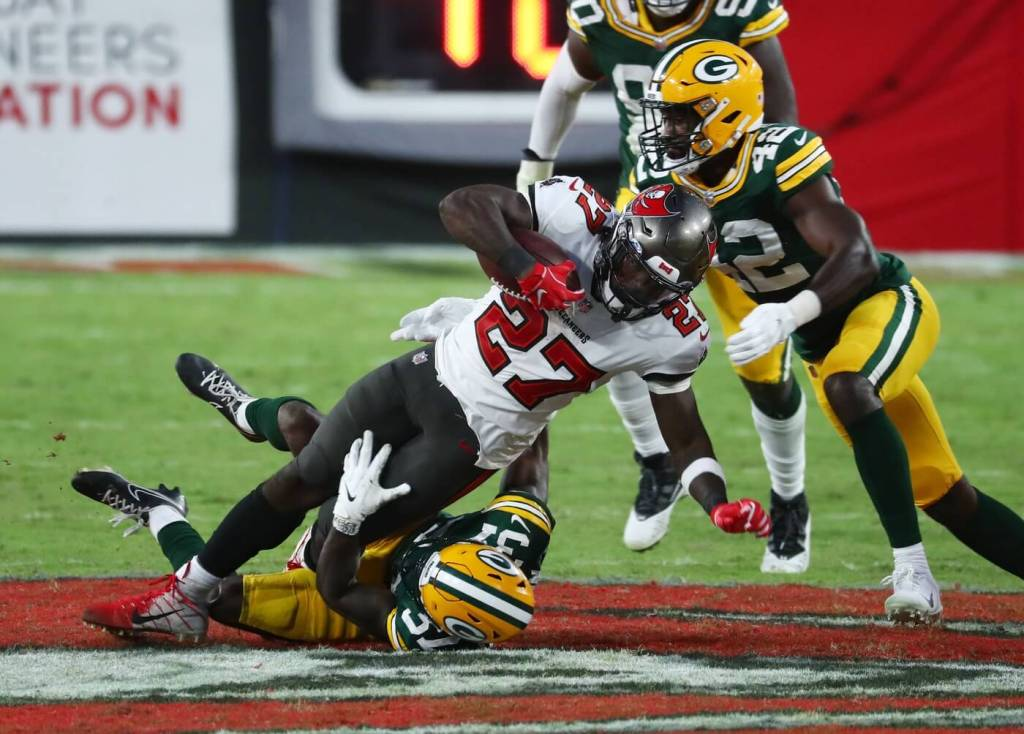 Tampa Bay Buccaneers running back Ronald Jones (27) is tackled by Green Bay Packers cornerback Josh Jackson (37) and inside linebacker Oren Burks (42) during the fourth quarter of a NFL game at Raymond James Stadium.