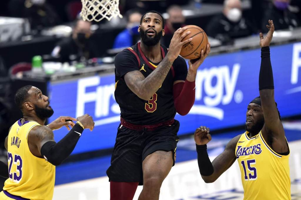 Cleveland Cavaliers center Andre Drummond (3) drives between Los Angeles Lakers forward LeBron James (23) and center Montrezl Harrell (15) in the first quarter at Rocket Mortgage FieldHouse.