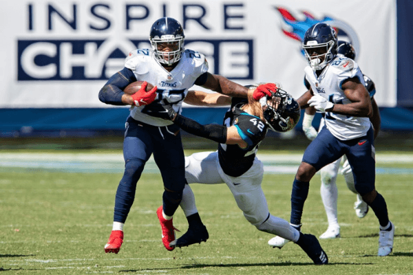 Derrick Henry #22 of the Tennessee Titans runs the ball and stiff arms Andrew Wingard #42 of the Jacksonville Jaguars at Nissan Stadium on September 20, 2020 in Nashville, Tennessee. The Titans defeated the Jaguars 33-30.