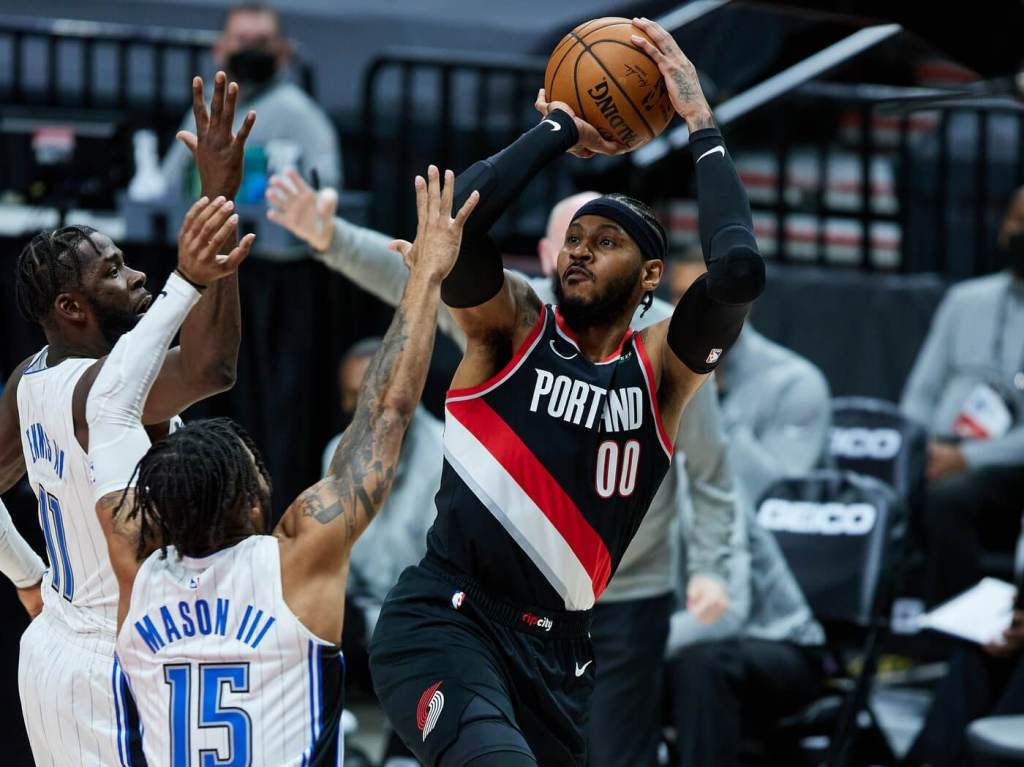 Portland Trail Blazers forward Carmelo Anthony (00) shoots the ball over Orlando Magic guard Frank Mason III (15) and forward James Ennis III (11) during the second quarter at the Moda Center.