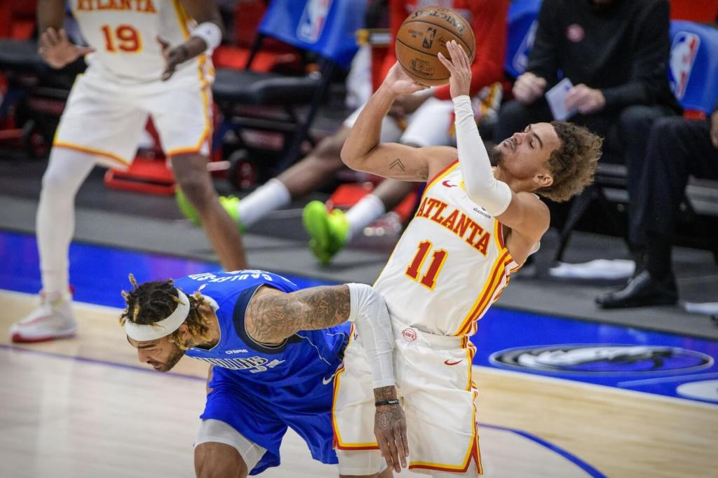 Feb 10, 2021; Dallas, Texas, USA; Atlanta Hawks guard Trae Young (11) is fouled by Dallas Mavericks center Willie Cauley-Stein (33) during the second half at the American Airlines Center. Mandatory Credit: Jerome Miron-USA TODAY Sports