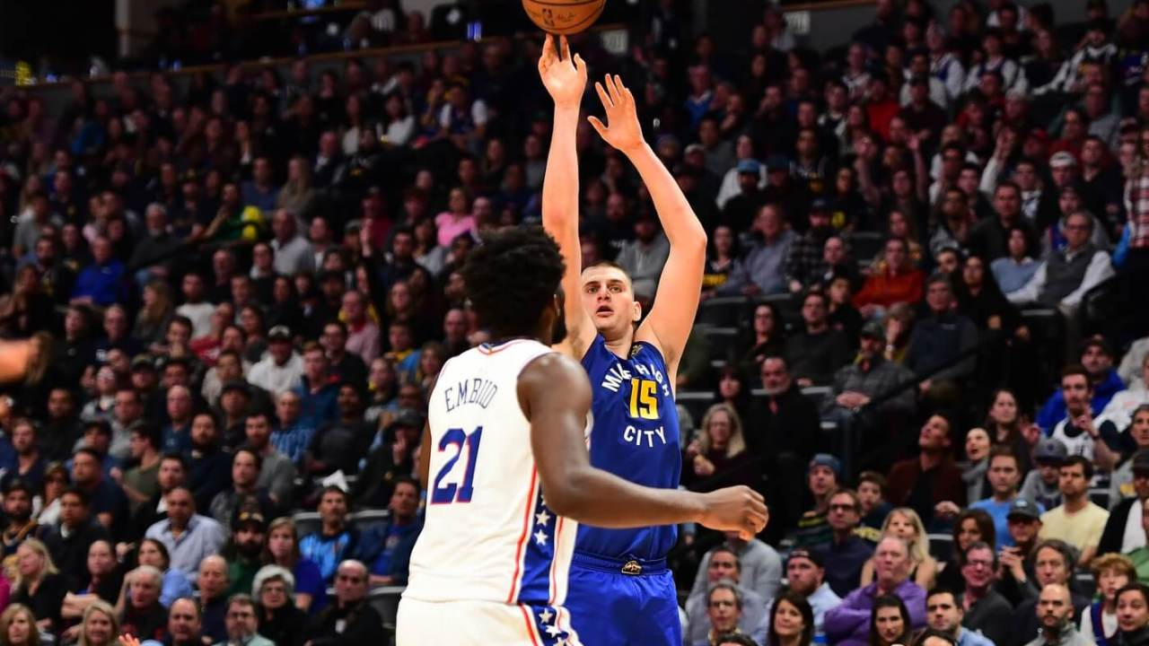 Nov 8, 2019; Denver, CO, USA; Denver Nuggets center Nikola Jokic (15) releases a three point basket attempt over Philadelphia 76ers center Joel Embiid (21) in the fourth quarter at the Pepsi Center. Mandatory Credit: Ron Chenoy-USA TODAY Sports