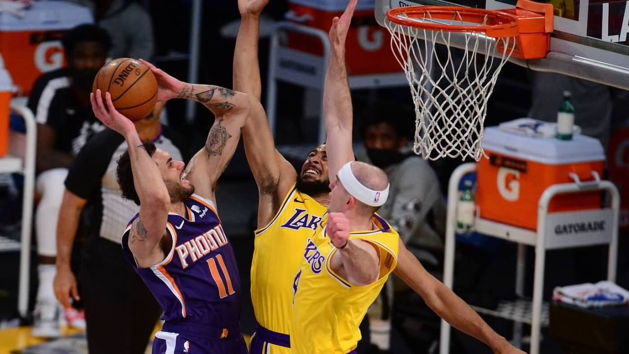 Phoenix Suns forward Abdel Nader (11) moves to the basket against Los Angeles Lakers guard Talen Horton-Tucker (5) and guard Alex Caruso (4) during the second half at Staples Center.