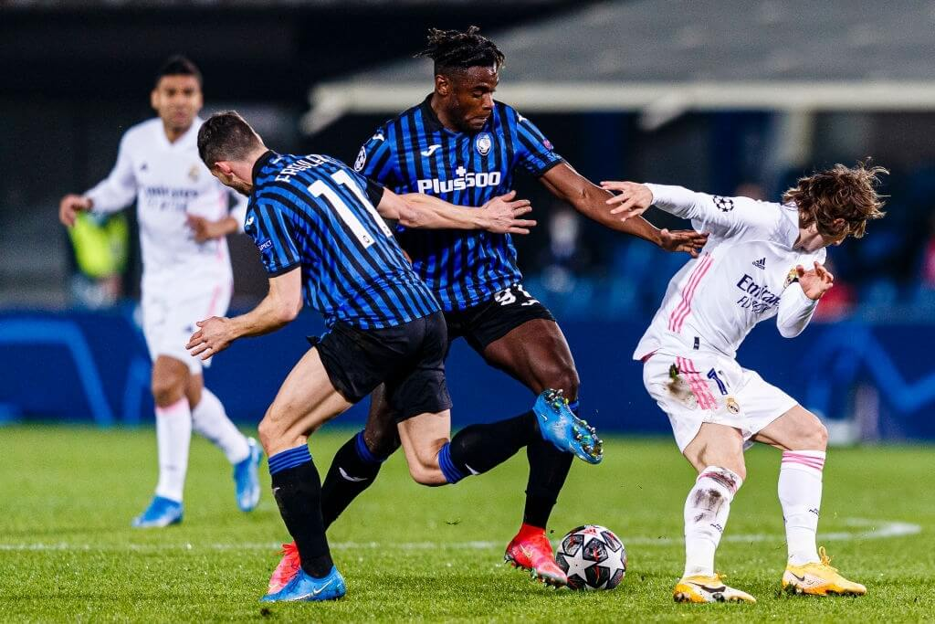 BERGAMO, ITALY - FEBRUARY 24: Duvan Zapata (C) and Remo Freuler of Atalanta (L) battles for the ball with Luka Modric of Real Madrid (R) during the UEFA Champions League Round of 16 match between Atalanta and Real Madrid at Gewiss Stadium on February 24, 2021 in Bergamo, Italy. (Photo by Ricardo Nogueira/Eurasia Sport Images/Getty Images)