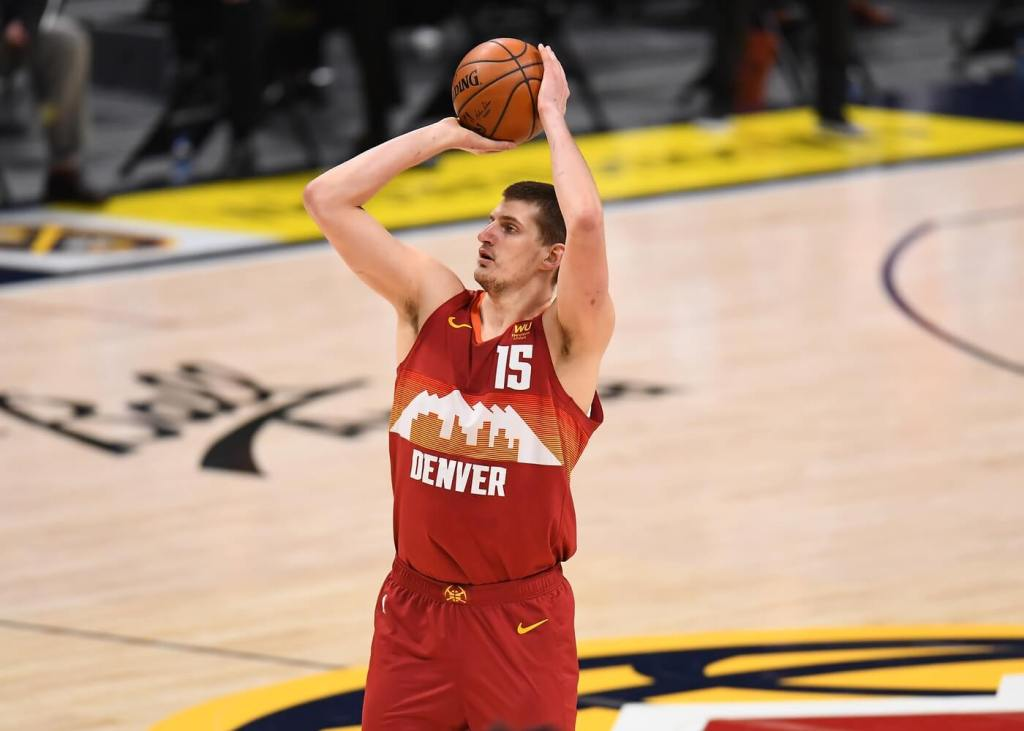 Feb 23, 2021; Denver, Colorado, USA; Denver Nuggets center Nikola Jokic (15) lines up a three point basket in the second quarter against the Portland Trail Blazers at Ball Arena. Mandatory Credit: Ron Chenoy-USA TODAY Sports