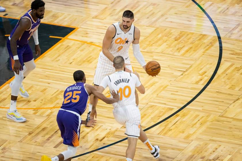 Mar 24, 2021; Orlando, Florida, USA; Orlando Magic center Nikola Vucevic (9) hands off the ball to guard Evan Fournier (10) during the third quarter of a game between the Phoenix Suns and the Orlando Magic at Amway Center. Mandatory Credit: Mary Holt-USA TODAY Sports