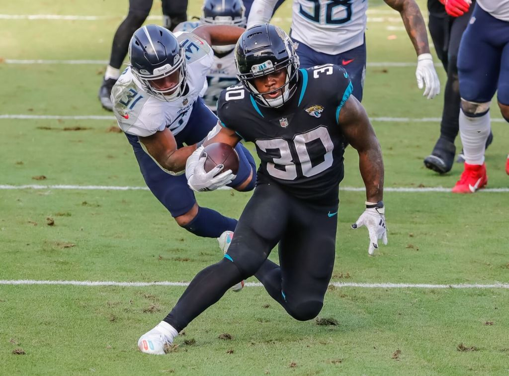 Dec 13, 2020; Jacksonville, Florida, USA; Jacksonville Jaguars running back James Robinson (30) carries the ball past Tennessee Titans free safety Kevin Byard (31) during the second half at TIAA Bank Field. Mandatory Credit: Mike Watters-USA TODAY Sports