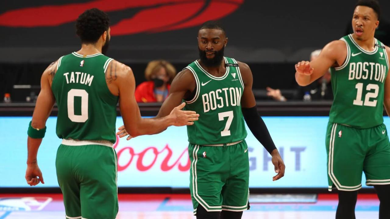 Jan 4, 2021; Tampa, Florida, USA; Boston Celtics forward Jayson Tatum (0) and guard Jaylen Brown (7) and forward Grant Williams (12) high five during the second quarter against the Toronto Raptors at Amalie Arena. Mandatory Credit: Kim Klement-USA TODAY Sports