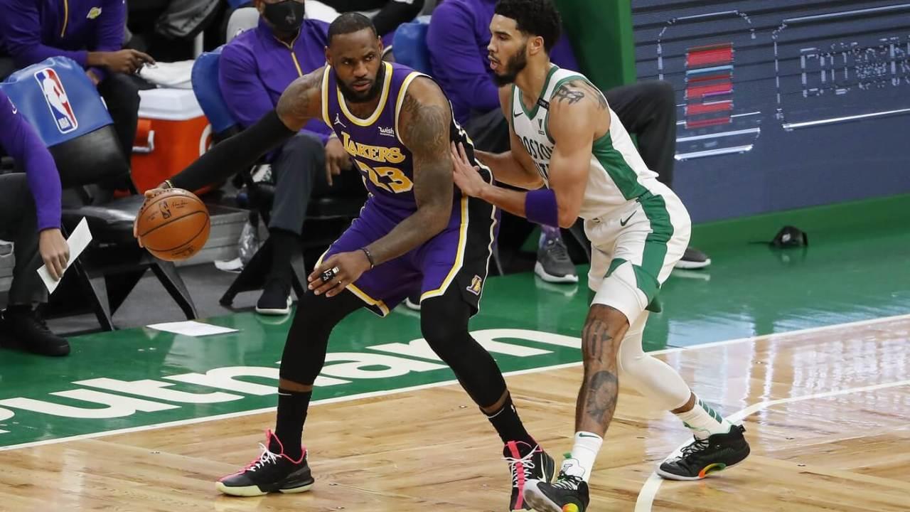 Jan 30, 2021; Boston, Massachusetts, USA; Los Angeles Lakers forward LeBron James (23) works on Boston Celtics forward Jayson Tatum (0) during the second quarter at TD Garden.