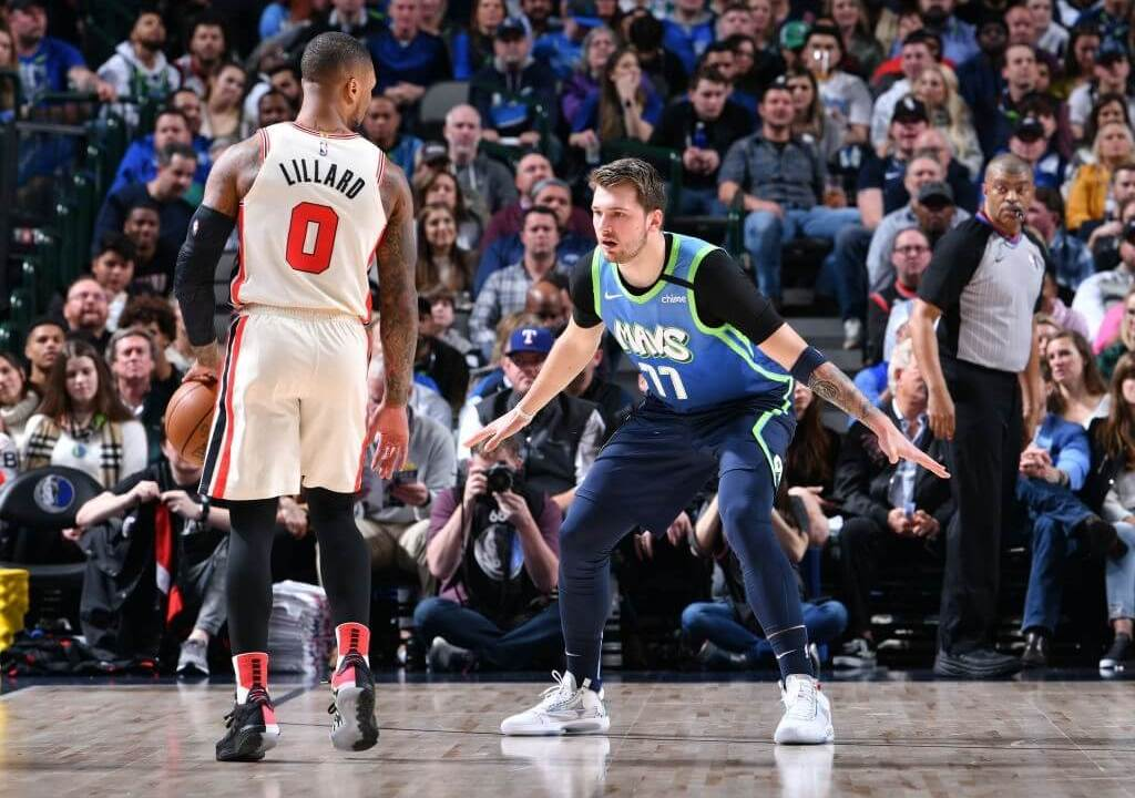 DALLAS, TX - JANUARY 17: Luka Doncic #77 of the Dallas Mavericks plays defense against Damian Lillard #0 of the Portland Trail Blazers on January 17, 2020 at the American Airlines Center in Dallas, Texas. NOTE TO USER: User expressly acknowledges and agrees that, by downloading and or using this photograph, User is consenting to the terms and conditions of the Getty Images License Agreement. Mandatory Copyright Notice: Copyright 2020 NBAE (Photo by Glenn James/NBAE via Getty Images)