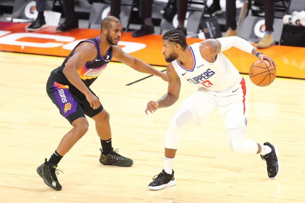 Jan 3, 2021; Phoenix, Arizona, USA; Los Angeles Clippers guard Paul George (13) dribbles against Phoenix Suns guard Chris Paul (3) in the second half at Phoenix Suns Arena. Mandatory Credit: Billy Hardiman-USA TODAY Sports
