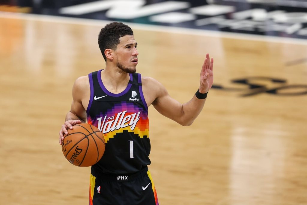 Mar 28, 2021; Charlotte, North Carolina, USA; Phoenix Suns guard Devin Booker (1) against the Charlotte Hornets during the second half at Spectrum Center. The Phoenix Suns won 101-97 in overtime. Mandatory Credit: Nell Redmond-USA TODAY Sports
