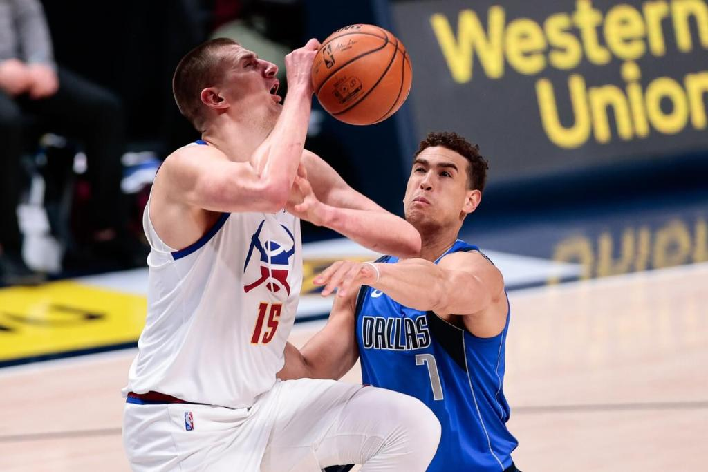 Mar 13, 2021; Denver, Colorado, USA; Denver Nuggets center Nikola Jokic (15) is fouled by Dallas Mavericks center Dwight Powell (7) in the first quarter at Ball Arena. Mandatory Credit: Isaiah J. Downing-USA TODAY Sports