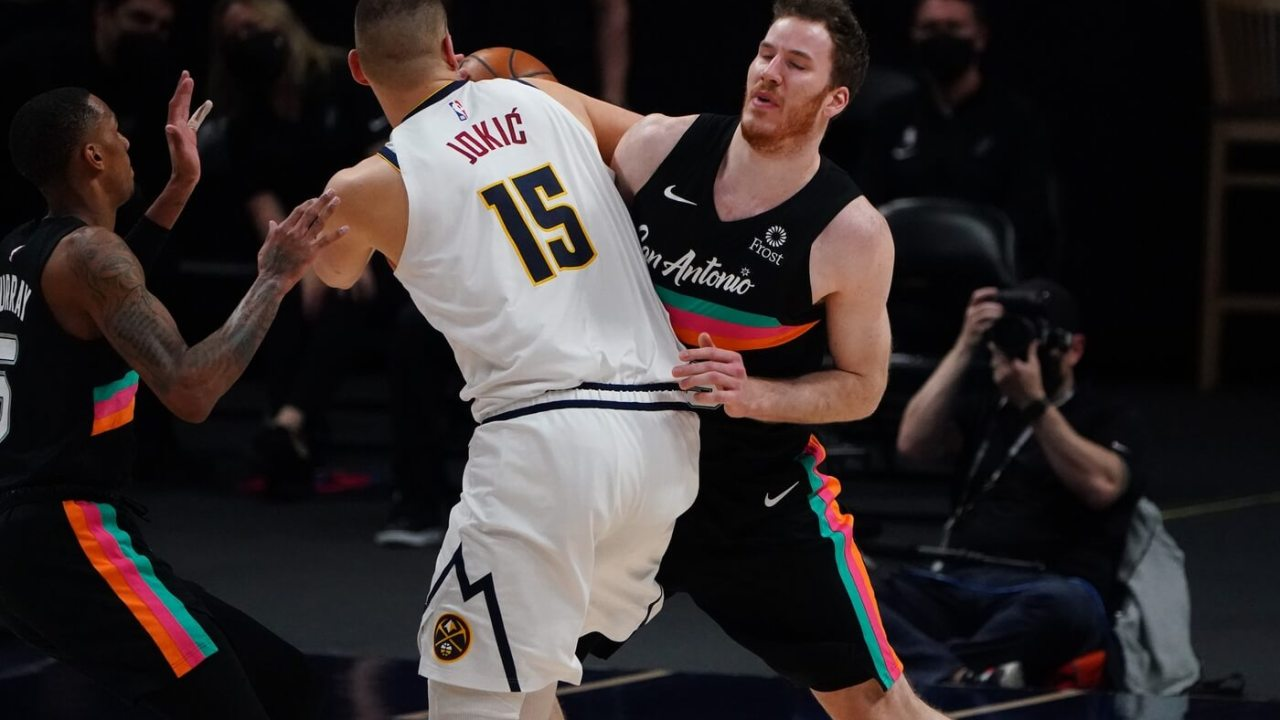 Apr 7, 2021; Denver, Colorado, USA; San Antonio Spurs center Jakob Poeltl (25) collides into Denver Nuggets center Nikola Jokic (15) in the second quarter at Ball Arena. Mandatory Credit: Ron Chenoy-USA TODAY Sports
