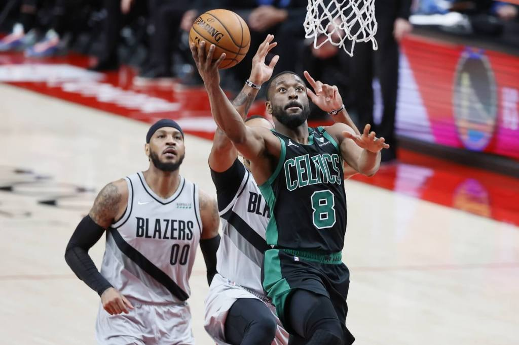 Apr 13, 2021; Portland, Oregon, USA; Boston Celtics point guard Kemba Walker (8) goes to the basket past Portland Trail Blazers small forward Norman Powell (24) during the second half at Moda Center. Mandatory Credit: Soobum Im-USA TODAY Sports