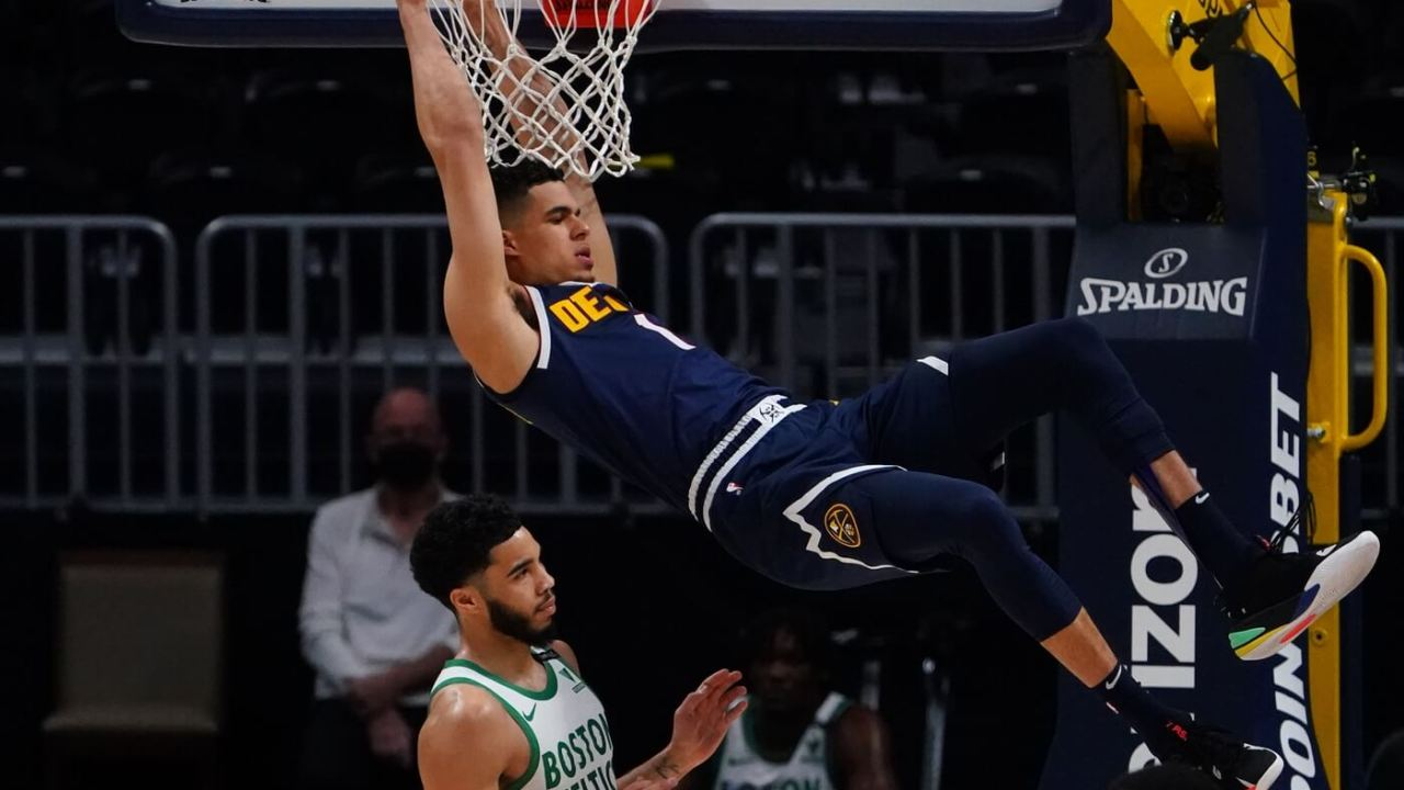 Apr 11, 2021; Denver, Colorado, USA; Denver Nuggets forward Michael Porter Jr. (1) finishes off a basket over Boston Celtics forward Jayson Tatum (0) in the second quarter at Ball Arena. Mandatory Credit: Ron Chenoy-USA TODAY Sports