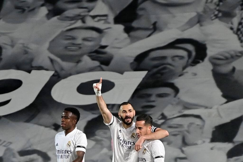 """TOPSHOT - Real Madrid's French forward Karim Benzema (C) celebrates with teammates after scoring during the """"El Clasico"""" Spanish League football match between Real Madrid CF and FC Barcelona at the Alfredo di Stefano stadium in Valdebebas, on the outskirts of Madrid on April 10, 2021."""