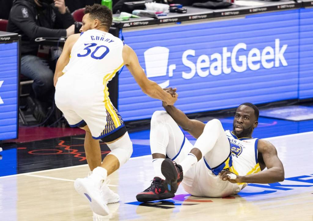 Apr 15, 2021; Cleveland, Ohio, USA; Golden State Warriors guard Stephen Curry (30) helps forward Draymond Green (23) up from the court during the third quarter against the Cleveland Cavaliers at Rocket Mortgage FieldHouse. Mandatory Credit: Scott Galvin-USA TODAY Sports