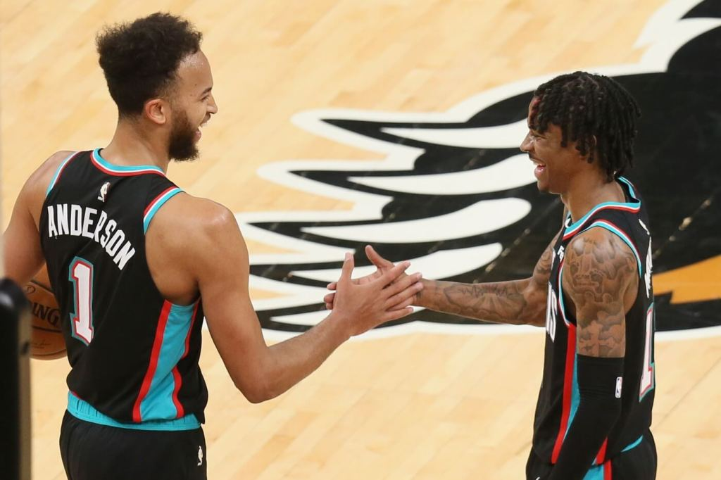 Mar 20, 2021; Memphis, Tennessee, USA; Memphis Grizzlies forward Kyle Anderson (1) celebrate with guard Ja Morant (12) after defeating the the Golden State Warriors at FedExForum. Grizzlies won 111-103. Mandatory Credit: Nelson Chenault-USA TODAY Sports