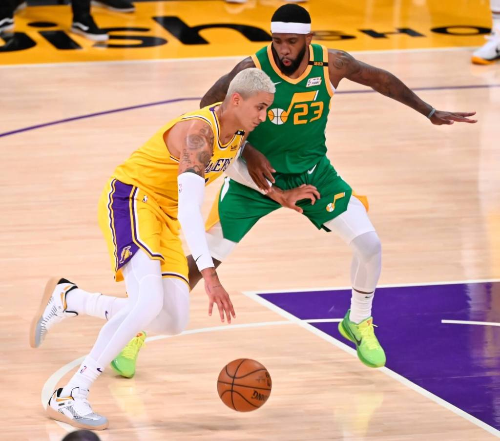 Apr 19, 2021; Los Angeles, California, USA; Los Angeles Lakers forward Kyle Kuzma (0) dribbles the ball past Utah Jazz forward Royce O'Neale (23) during the third quarter at Staples Center. Mandatory Credit: Robert Hanashiro-USA TODAY Sports