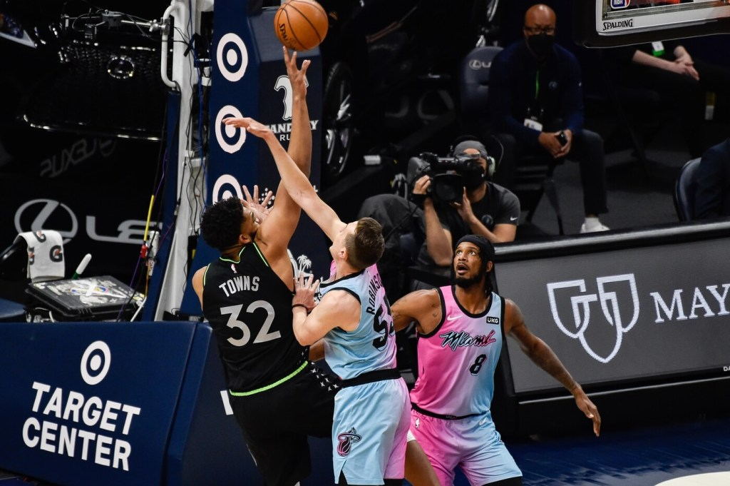 Apr 16, 2021; Minneapolis, Minnesota, USA; Miami Heat guard Duncan Robinson (55) and forward Trevor Ariza (8) defend the shot of Minnesota Timberwolves center Karl-Anthony Towns (32) during the first quarter at Target Center. Mandatory Credit: Jeffrey Becker-USA TODAY Sports