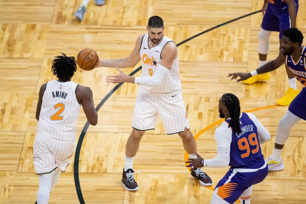 Mar 24, 2021; Orlando, Florida, USA; Orlando Magic center Nikola Vucevic  (9) hands off the ball to forward Al-Farouq Aminu (2) during the second quarter of a game between the Phoenix Suns and the Orlando Magic at Amway Center. Mandatory Credit: Mary Holt-USA TODAY Sports