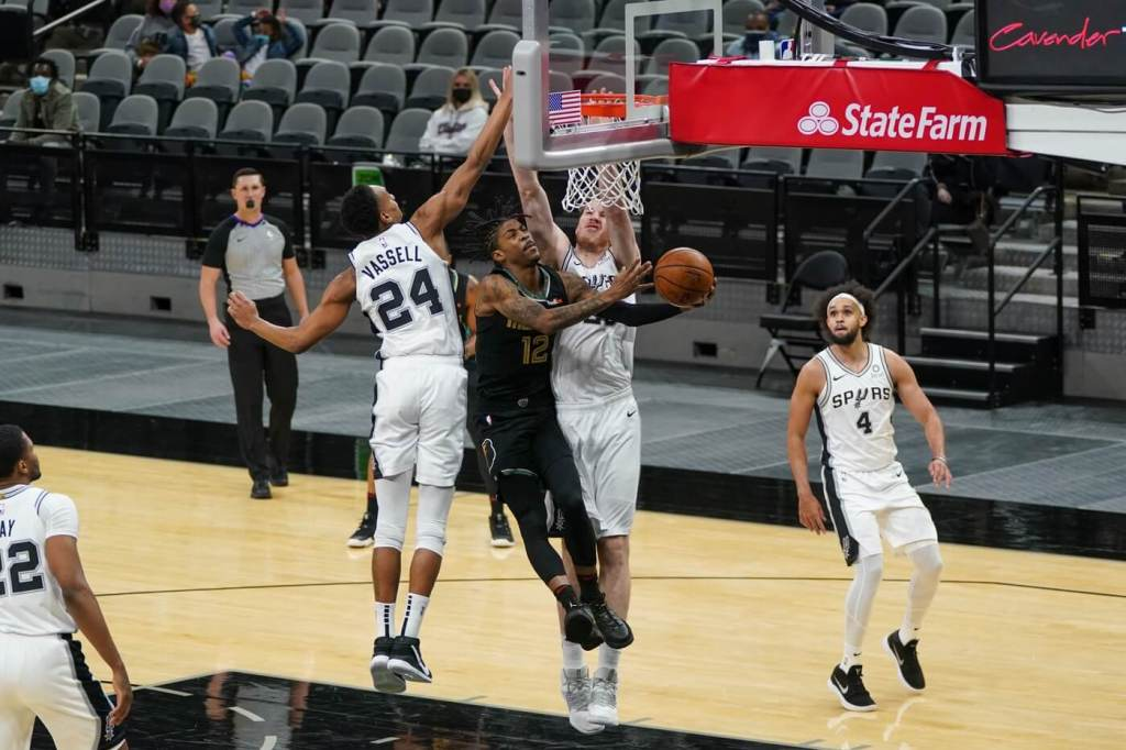 Jan 30, 2021; San Antonio, Texas, USA; Memphis Grizzlies guard Ja Morant (12) shoots around San Antonio Spurs guard Devin Vassell (24) and center Jakob Poeltl (25) in the first half at the AT&T Center. Mandatory Credit: Daniel Dunn-USA TODAY Sports