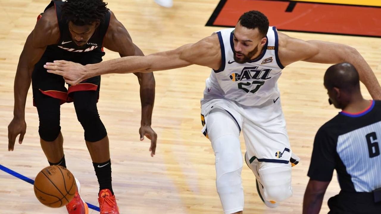 Feb 26, 2021; Miami, Florida, USA; Utah Jazz center Rudy Gobert (27) and Miami Heat forward Jimmy Butler (22) battle for a loose ball in the fourth quarter at American Airlines Arena. Mandatory Credit: Jim Rassol-USA TODAY Sports