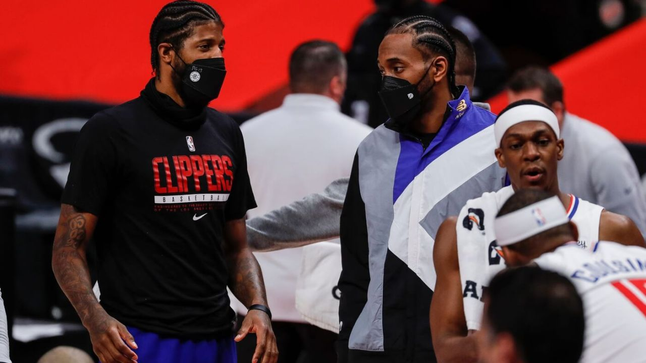 Clippers guard Paul George, left, talks to Kawhi Leonard at a timeout during the second half at the Little Caesars Arena on Wednesday, April 14, 2021.