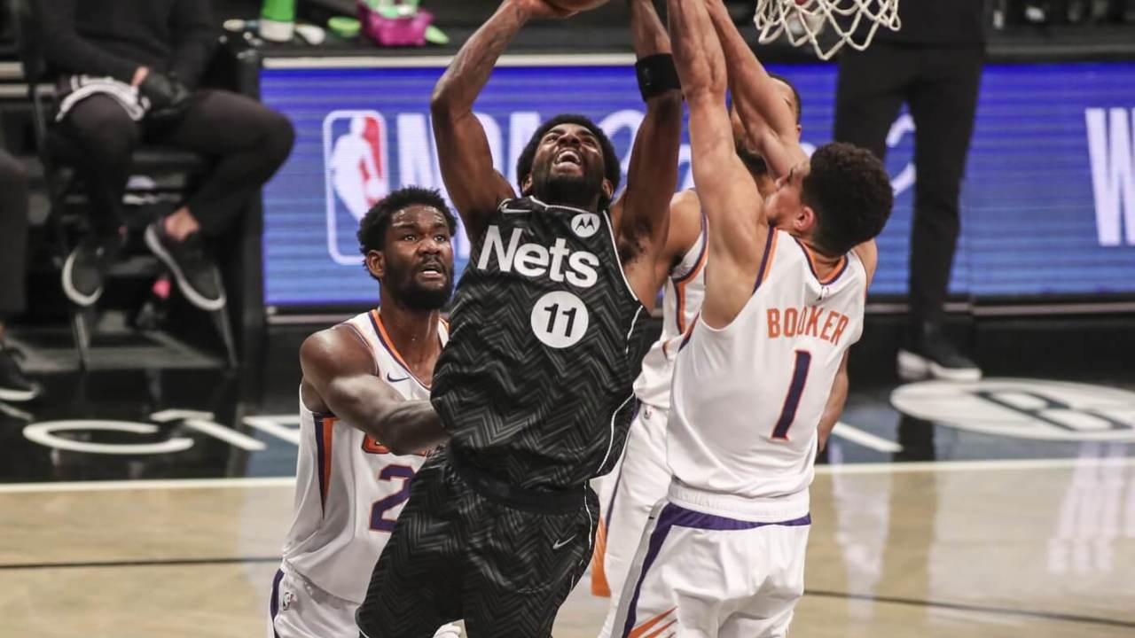 Apr 25, 2021; Brooklyn, New York, USA; Brooklyn Nets guard Kyrie Irving (11) goes up against Phoenix Suns guard Devin Booker (1) in the third quarter at Barclays Center. Mandatory Credit: Wendell Cruz-USA TODAY Sports