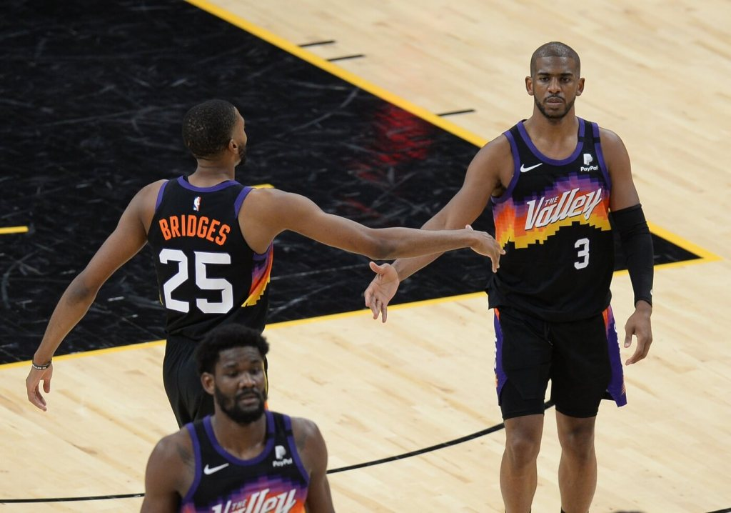Apr 28, 2021; Phoenix, Arizona, USA; Phoenix Suns forward Mikal Bridges (25) and Phoenix Suns guard Chris Paul (3) slap hands during the second half against the LA Clippers at Phoenix Suns Arena. Mandatory Credit: Joe Camporeale-USA TODAY Sports