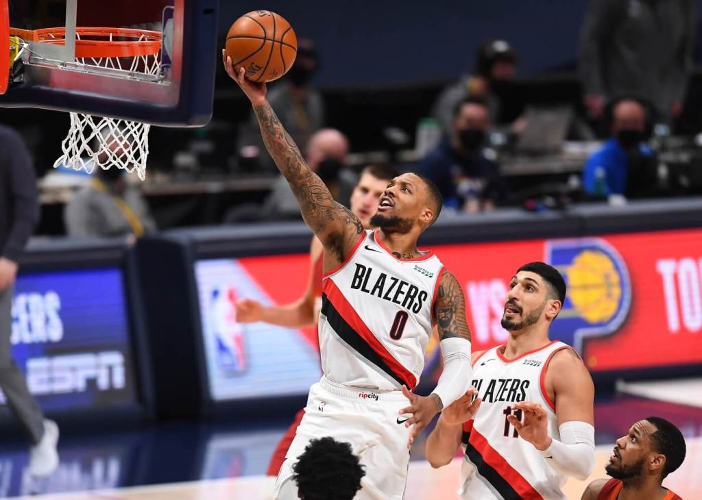 Feb 23, 2021; Denver, Colorado, USA; Portland Trail Blazers guard Damian Lillard (0) finishes of a basket in the fourth quarter against the Denver Nuggets at Ball Arena. Mandatory Credit: Ron Chenoy-USA TODAY Sports