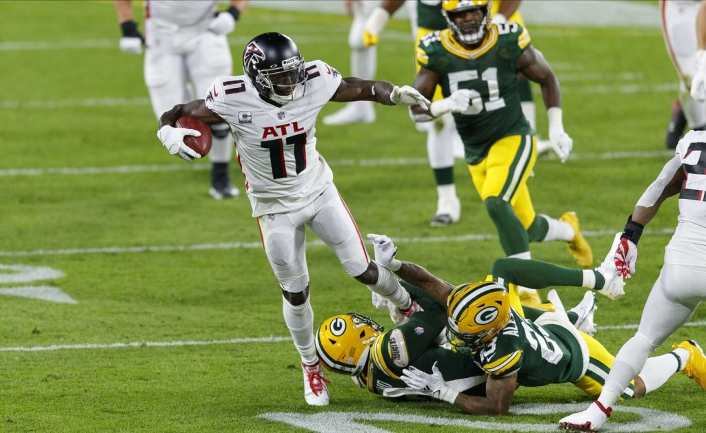 Oct 5, 2020; Green Bay, Wisconsin, USA; Atlanta Falcons wide receiver Julio Jones (11) is tackled after catching a pass during the second quarter against the Green Bay Packers at Lambeau Field. Mandatory Credit: Jeff Hanisch-USA TODAY Sports