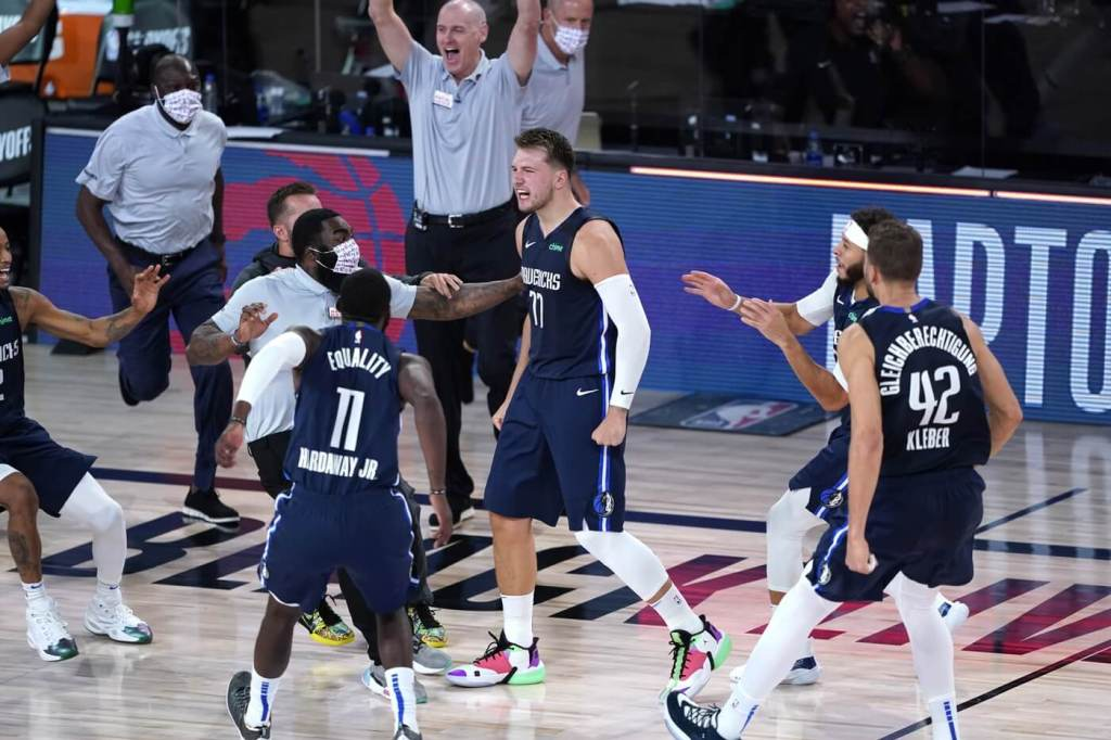 Aug 23, 2020; Lake Buena Vista, Florida, USA; Dallas Mavericks' Luka Doncic (77) celebrates with teammates after making a game-winning 3-point basket against the Los Angeles Clippers during overtime of an NBA basketball first round playoff game at AdventHealth Arena. Mandatory Credit: Ashley Landis/Pool Photo-USA TODAY Sports