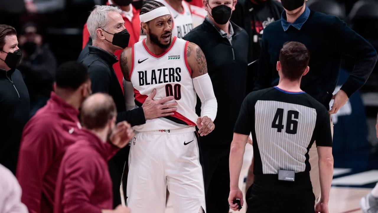 May 24, 2021; Denver, Colorado, USA; Portland Trail Blazers forward Carmelo Anthony (00) is held back by assistant coach John McCullough (L) as he argues a call with referee Ben Taylor (46) at the end of the second quarter against the Denver Nuggets during game two in the first round of the 2021 NBA Playoffs at Ball Arena.